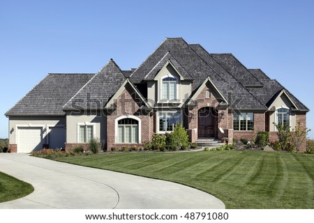 Luxury brick home with cedar shake roof - stock photo
