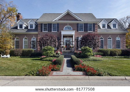 Luxury brick home with column entry and flowers - stock photo