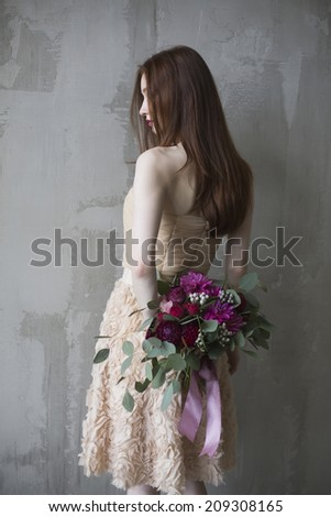 Luxury bride in a pink dress with a wedding bouquet in the wine color - stock photo