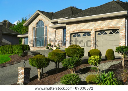 luxury  bungalow house and garage with ornamental  landscaping garden and paved driveway - stock photo
