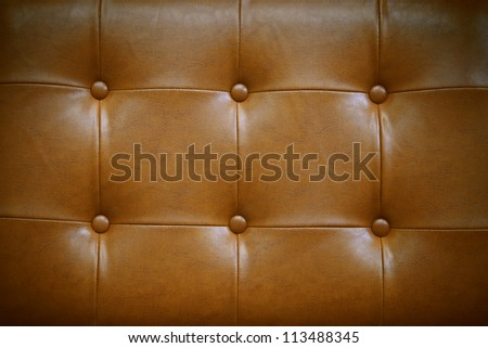 luxury button decorated on brown leather use as high class background - stock photo