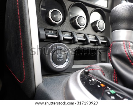 luxury car interior gearshift and and air conditioning knobs silhouette close up - stock photo