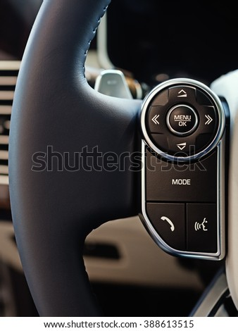 Luxury car interior: multimedia system control buttons on the steering wheel, shallow depth of field