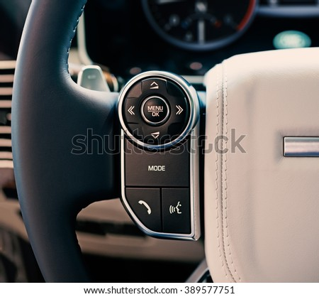 Luxury car interior: multimedia system control buttons on the steering wheel, shallow depth of field - stock photo