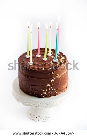 Luxury chocolate cake with edible gold glitter on white cake stand. Isolated on white background. Birthday candles.