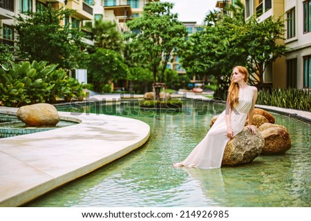 Luxury city lifestyle beautiful woman in hotel resort swimming pool - stock photo