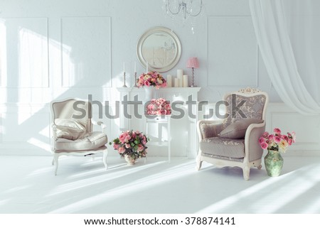 luxury clean bright white interior. a spacious room with sunlight and flowers in vases - stock photo