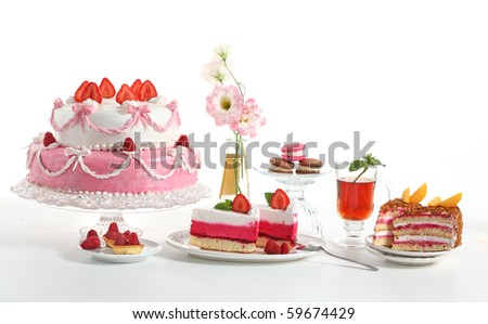 Luxury composition with a pie, tea, fruit cakes and flowers. - stock photo