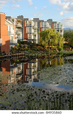 Luxury condominiums in the early morning light reflect in a still pond. Vancouver, British Columbia, Canada. - stock photo