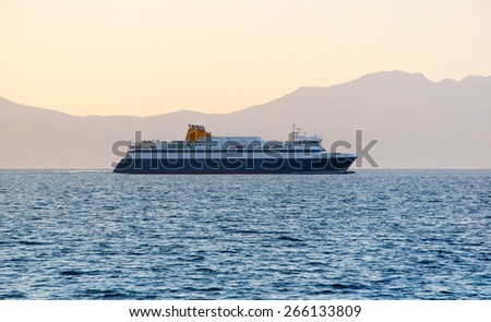 Luxury cruise ship sailing from port of island - stock photo