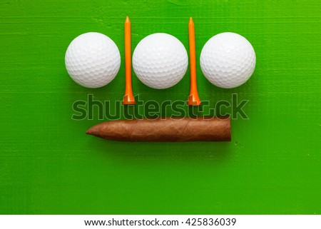 Luxury Cuban cigar and golf equipments on the wooden green table - stock photo
