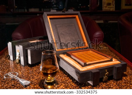 luxury Cuban cigars in a box and a glass of alcohol - stock photo