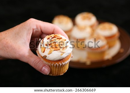 Luxury Cup Cakes with almond chips and cream topping being held by female hand - stock photo