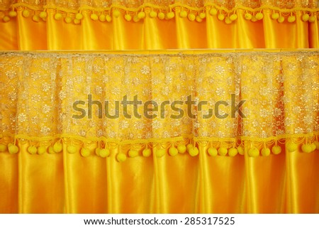 Luxury curtains with gold peach lace sits on a gold silk background - stock photo