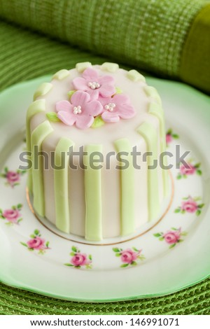 Luxury decorated mini cake with pink petals on a green background - stock photo