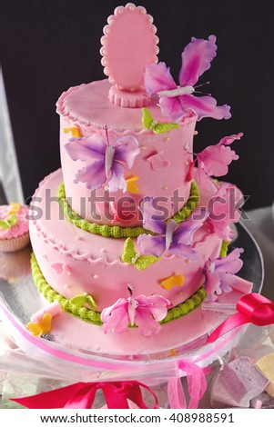 luxury delicious pink cake with colorful butterflies and candy bar at celebration, party in a restaurant - stock photo