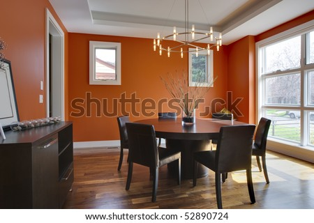 Luxury Dining Room with Orange Walls. Brightly lit with large windows. - stock photo
