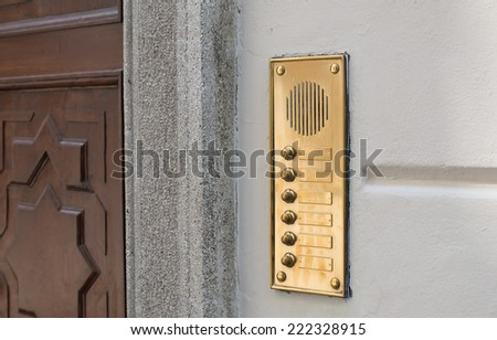 Luxury door intercom and bell buttons in brass with wooden door - stock photo
