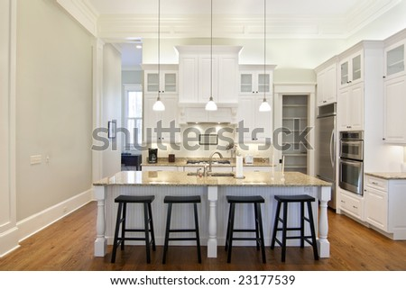luxury eat-in kitchen with white cabinets and granite counters - stock photo