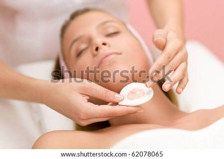 Luxury facial care - woman in spa salon receiving beauty treatment