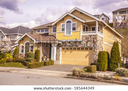 luxury family house with landscaping on the front and blue sky on background and green grass on front   - stock photo