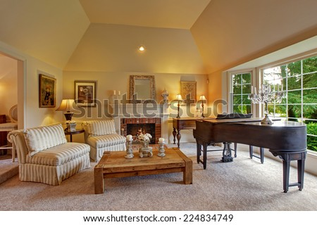 Luxury family room with high vaulted ceiling and large french window. Room has grand piano, fireplace, striped chairs and wooden coffee table - stock photo