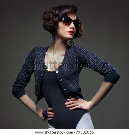 Luxury Fashion model, a beautiful woman posing in studio on gray background with glasses from the sun