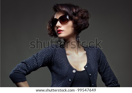 Luxury Fashion model, a beautiful woman posing in studio on gray background with glasses from the sun - stock photo