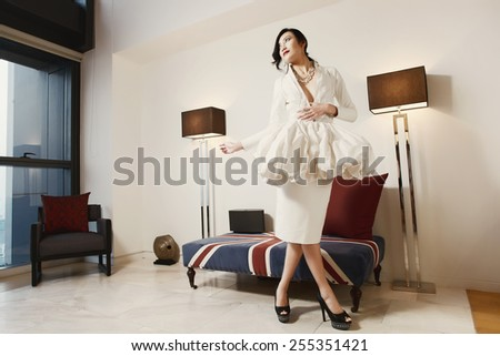 Luxury fashion style model in living room interior - stock photo