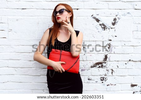 luxury fashion young woman looking away and posing in black fashionable dress , sunglasses, red handbag near street white wall - stock photo