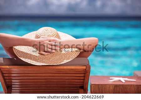 Luxury female tanning on the beach, wearing big stylish hat, enjoying beautiful seascape, summer fashion, travel and tourism concept - stock photo