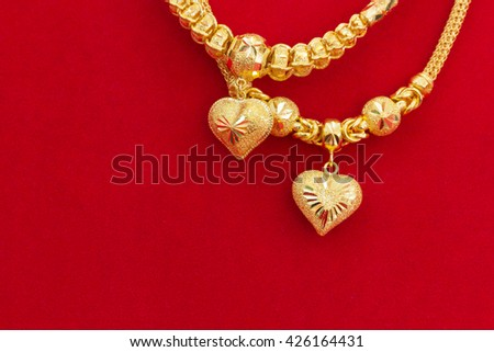 Luxury gold necklaces on red flannel,with copy space, gold ornament, gold bar, gold accessory, gold accessories, gold bracelet, gold necklace, gold Asian, gold shop, gold background, gold pendant. - stock photo