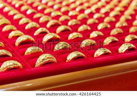 Luxury gold rings on red flannel, gold ornament, gold bar, gold accessory, gold accessories, gold bracelet, gold ring, gold necklace, gold asian, gold shop, gold golden background, gold pendant. - stock photo