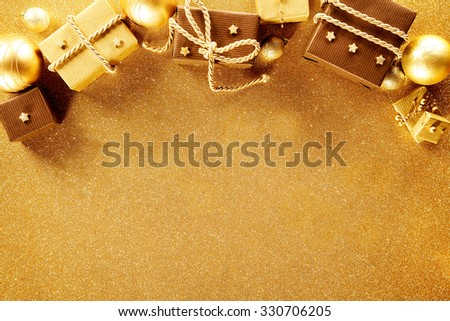 Luxury gold themed Christmas border with assorted decorative gifts and baubles on a textured gold background with copyspace for your seasonal greeting - stock photo