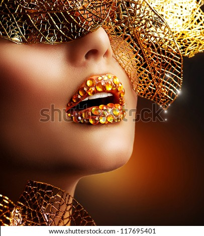 Luxury Golden Makeup. Beautiful Professional Holiday Make-up. Sexy Gold Lips.Fashion Art Portrait.Jewelry - stock photo