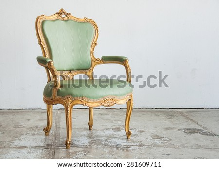 Luxury green vintage style armchair sofa in a vintage room - stock photo