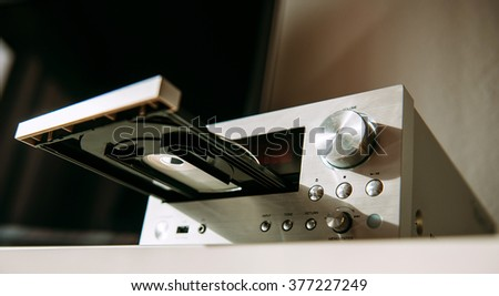 Luxury Hi-Fi stereo amplifier tuner with CD tray open as seen from lateral low angle - stock photo