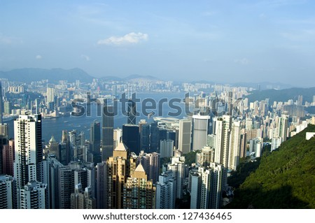 Luxury hilltop looking out over the dramatic night time neon lights and illuminated skyscrapers, crowded high-rise apartment blocks and futuristic architecture of Hong Kong Island from Victoria Peak - stock photo