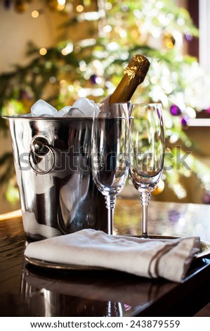 Luxury holiday table setting, a bottle of chilled champagne in an ice bucket and elegant glasses, festive lights in the background