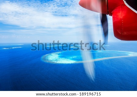 Luxury holidays, flight to resort on a little red water airplane, flight over beautiful blue sea, aerial scenic view, traveling and tourism concept - stock photo