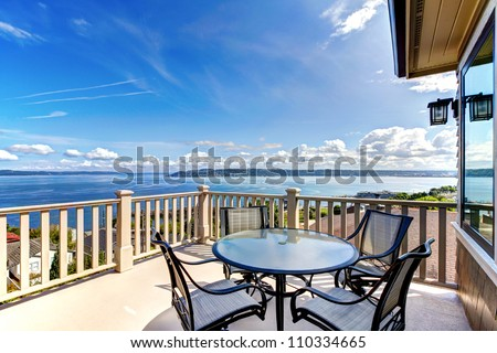 Luxury home balcony deck with water view and table with house. - stock photo