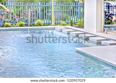 Luxury home entrance, colorful water in swimming pool near luxury house, daytime scene with perfect lightning, ground is fully tiled, garden has wooden fence also beautiful trees.