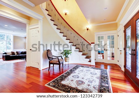 Luxury home entrance with cherry hardwood floor and staircase. - stock photo