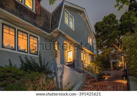 Luxury Home Exterior with house, garden, stone floor and wooden deck at twilight. - stock photo