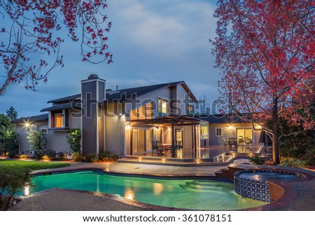 Luxury Home Exterior with illuminated pool and wooden deck at twilight. - stock photo