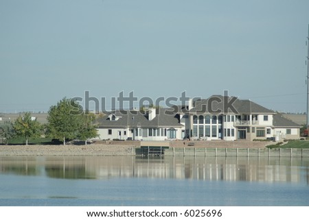 Luxury home in affluent neighborhood on a lake - stock photo