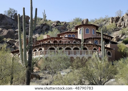 Luxury home in desert with front deck and cactus - stock photo