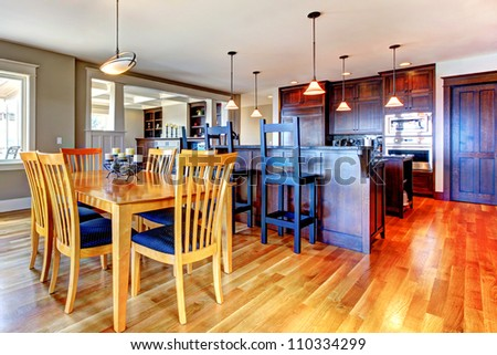 Luxury home kitchen and dining room with open floor plan and rich wood. - stock photo