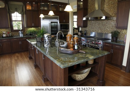 Luxury home kitchen with a hardwood floor and granite island. - stock photo