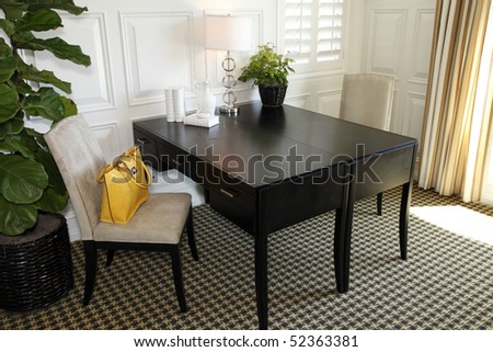 Luxury home office with modern decor and coach handbag. - stock photo